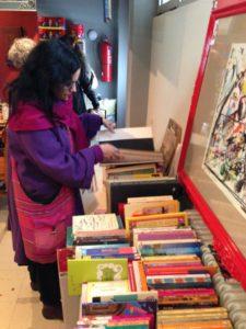 επισκέπτρια ξεφυλλίζει βιβλία στο Bazaar των Δρόμων Ζωής